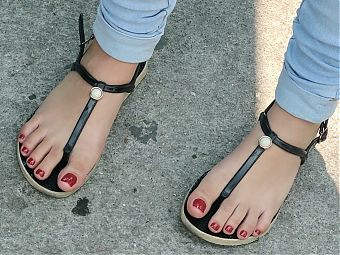 little girl feet with red nails sandals